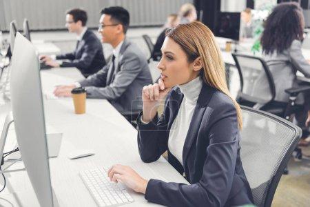 Photo pour Jeune femme d'affaires concentrée utilisant un ordinateur de bureau tout en travaillant avec des collègues dans un bureau ouvert - image libre de droit