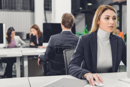 Photo pour Belle femme jeune ciblée assis au milieu de travail et à l'aide d'ordinateur de bureau - image libre de droit