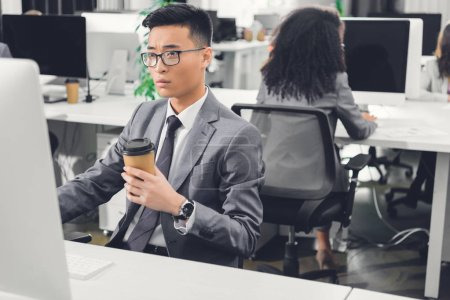 serious young asian businessman holding coffee to go in using desktop computer in office