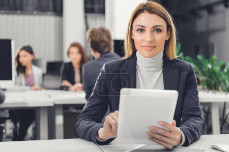beautiful young businesswoman holding digital tablet and smiling at camera in office
