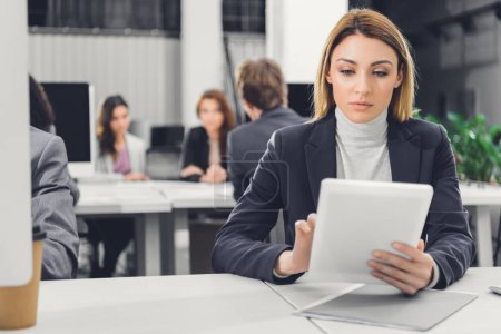 Photo for Focused young businesswoman using digital tablet while working with colleagues in open space office - Royalty Free Image
