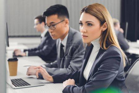 Photo pour Axé sur la jeune femme regardant d'ordinateur de bureau et de travailler avec des collègues de bureau - image libre de droit