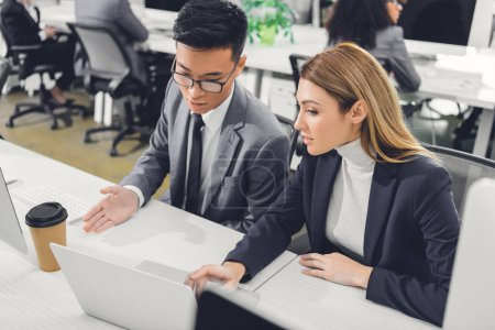 focused young businesspeople discussing work and pointing at laptop in office