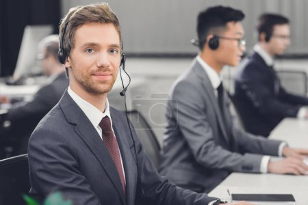 Photo for Handsome young businessman in headset smiling at camera while working with colleagues in office - Royalty Free Image
