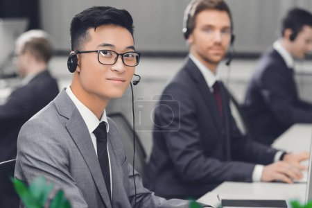 Photo for Handsome young asian businessman in headset smiling at camera while working with colleagues in call center - Royalty Free Image