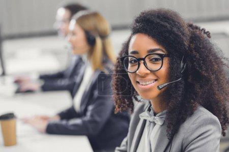 belle jeune femme afro-américaine en casque souriant à la caméra tout en travaillant avec des collègues au bureau