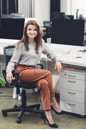 Photo pour Belle femme jeune heureuse assis au milieu de travail et souriant à la caméra dans le bureau - image libre de droit