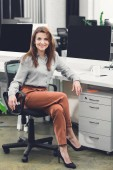 beautiful happy young businesswoman sitting at workplace and smiling at camera in office