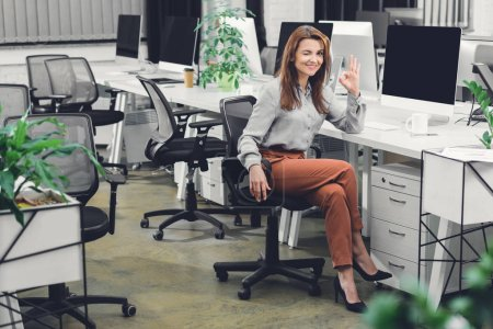 happy young businesswoman showing ok sign and smiling at camera in office