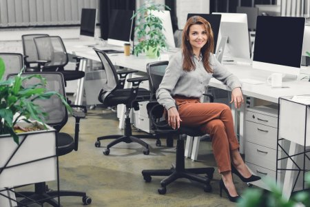 attractive young businesswoman sitting at workplace and smiling at camera