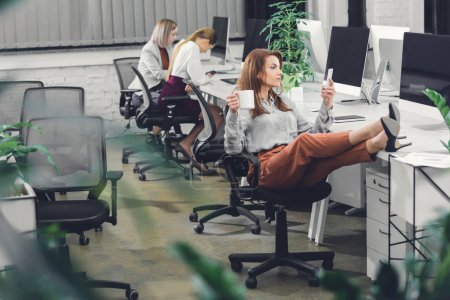 beautiful young businesswoman holding cup and using smartphone while sitting with legs on desk in open space office