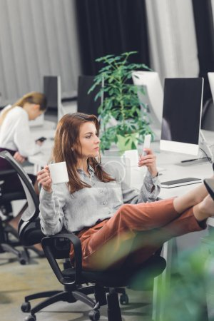 attractive young businesswoman holding cup and using smartphone while sitting in office