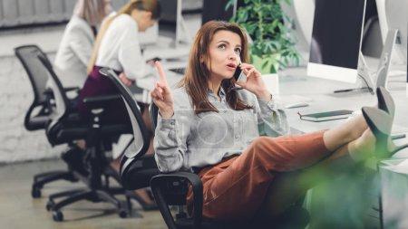 Photo pour Belle jeune femme d'affaires vers le haut avec le doigt et parler de smartphone au bureau - image libre de droit