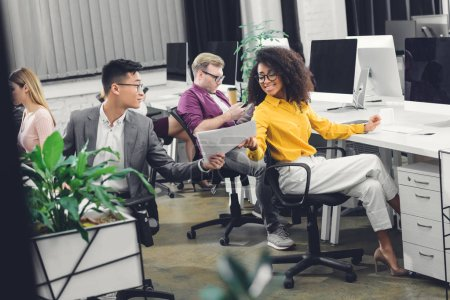 smiling young multiracial businesspeople holding papers and working together in office