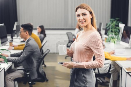 beautiful young businesswoman with cup and smartphone smiling at camera while colleagues working behind in office