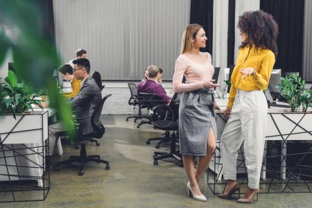 young multiethnic businesswomen talking and smiling each other while colleagues working behind in office