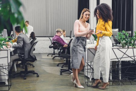 smiling young businesswomen using smartphone and talking while colleagues working behind in office