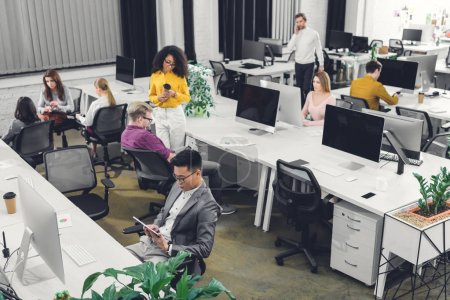 high angle view of multiethnic group of businesspeople working together in open space office