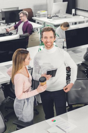 high angle view of happy businesswoman with coffee to go and smiling businessman standing together in office