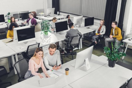 high angle view of young business colleagues sitting and working together in open space office