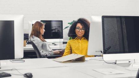 Foto de Hermosa buisnesswoman afroamericano en gafas sonriendo a la cámara mientras está sentado en el lugar de trabajo - Imagen libre de derechos