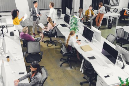 high angle view of professional young businesspeople working together in open space office