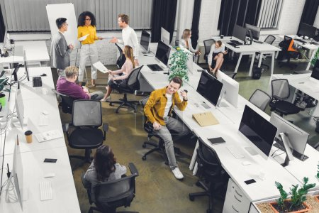 high angle view of young business colleagues working with papers and computers in open space office