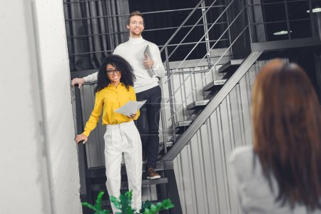 multiethnic young businesspeople standing on staircase and smiling in modern office