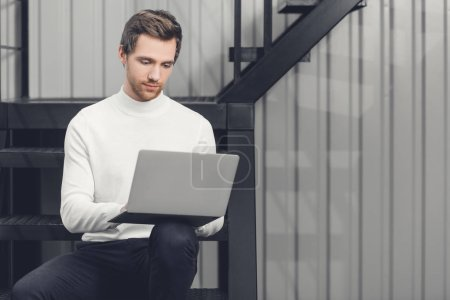 handsome smiling young man sitting on stairs and using laptop in office