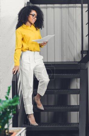 Photo pour Belle souriante jeune afro-américaine femme d'affaires détenant des documents et permanent dans les escaliers au bureau - image libre de droit