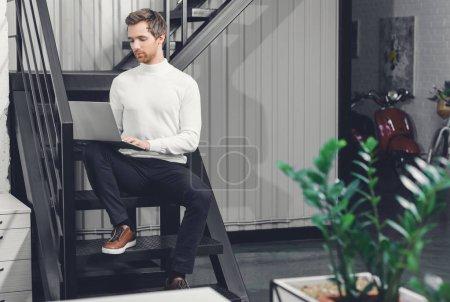 Photo pour Concentré de jeune homme assis dans les escaliers et utilisez l'ordinateur portable au bureau - image libre de droit