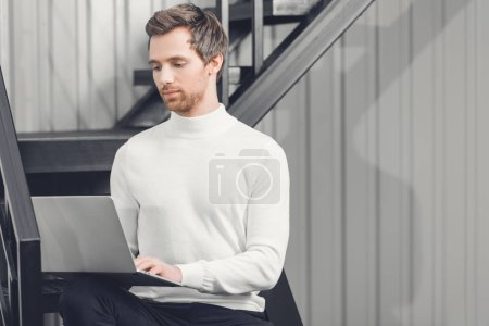 focused young businessman sitting on stairs and using laptop in office
