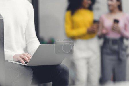Foto de Tiro corto de hombre de negocios sentado y usando laptop mientras colegas sosteniendo las tazas de papel detrás en oficina - Imagen libre de derechos