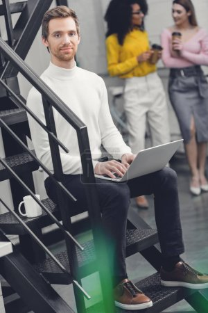 handsome man sitting with laptop on stairs and smiling at camera while female colleagues drinking coffee behind in office