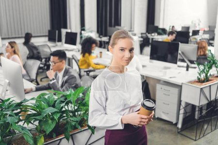 Photo for Beautiful young businesswoman holding coffee to go and smiling at camera while colleagues working behind in open space office - Royalty Free Image