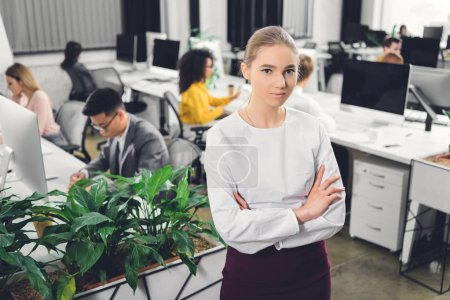 beautiful young businesswoman standing with crossed arms and looking at camera in open space office