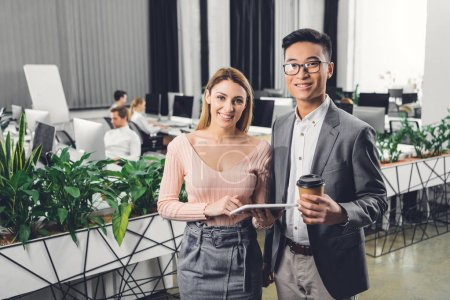 cheerful young businesspeople with digital tablet and coffee to go smiling at camera in office