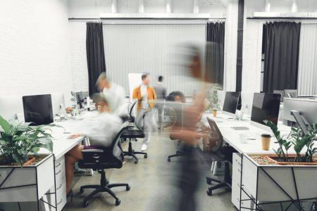 Photo for Contemporary open space office interior with blurred coworkers in motion - Royalty Free Image
