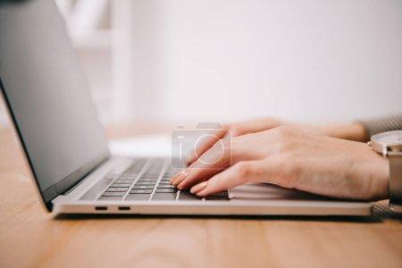 Photo pour Recadrée vue de femme d'affaires, dactylographie sur ordinateur portable à l'espace de travail - image libre de droit