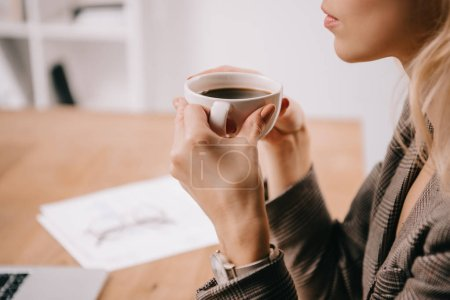 cropped view of businesswoman holding cup of coffee on break in office
