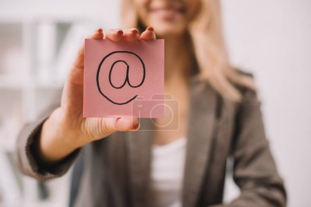 selective focus of businesswoman holding paper note with email sign