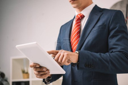cropped view of businessman using digital tablet in office