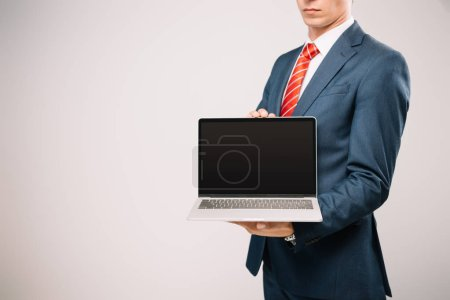 Foto de Recorta la vista del hombre de negocios en traje mostrando portátil aislado en gris - Imagen libre de derechos