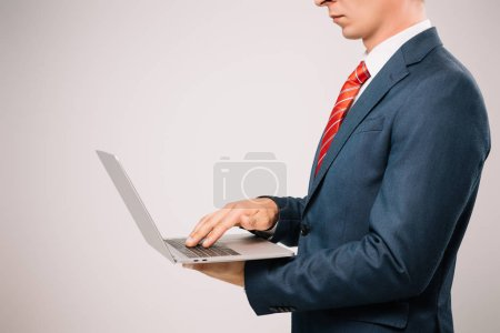 Photo for Cropped view of businessman in suit using laptop isolated on grey - Royalty Free Image