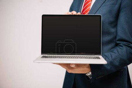 cropped view of businessman in suit presenting laptop with blank screen isolated on grey
