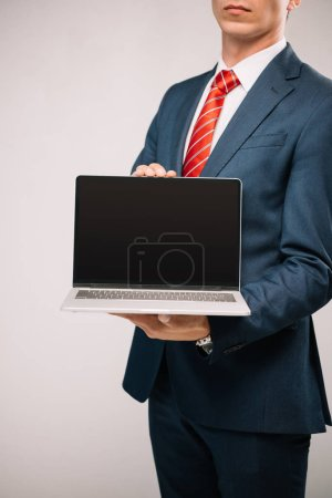 cropped view of businessman in suit presenting laptop isolated on grey