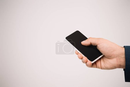Photo for Cropped view of businessman using smartphone isolated on grey - Royalty Free Image