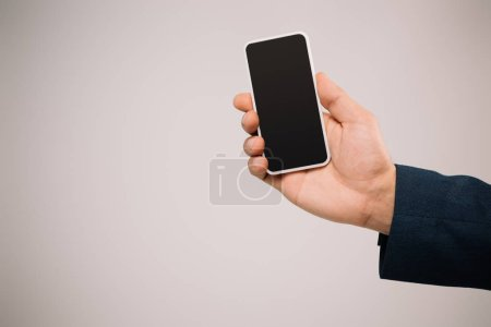 Photo for Cropped view of businessman holding smartphone with blank screen isolated on grey - Royalty Free Image