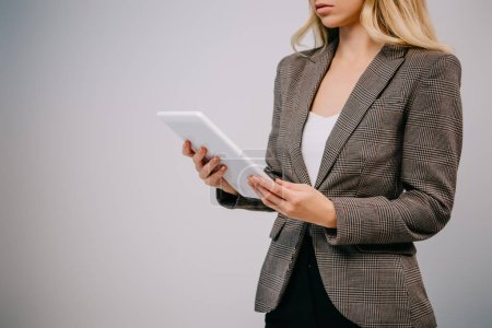 Photo for Cropped view on businesswoman in suit using tablet isolated on grey - Royalty Free Image