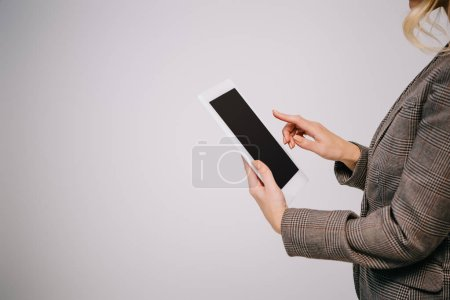 cropped view on businesswoman using digital tablet isolated on grey with blank screen